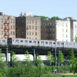 Alte Züge der New Yorker Subway auf der Hochbahn in der Bronx - im Hintergrund Wohnhäuser der Bronx