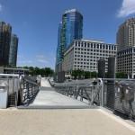 Blick von der Uferpromenade in Jersey City auf die grün-bläulich schimmernden Hochhäuser der 70 Greene Street
