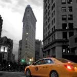 Flatiron Building mit gelbem NYC Taxi - in schwarz-weißer Umgebung