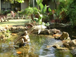 Skulpturen eines Delfins und einer Meerjungfrau in einem Teich