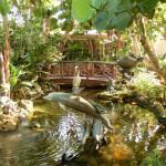 Teich mit Skulpturen und einer Holzbrücke im Hotel-Innenhof