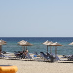 Sonnenschirme, Liegestühle und das blaue Meer am Strand von Keramoti