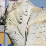 Skulptur an der Hafenpromenade mit drei schreinden Gesichtern