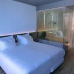 Doppelbett mit Blick auf das verpiegelte Badezimmer